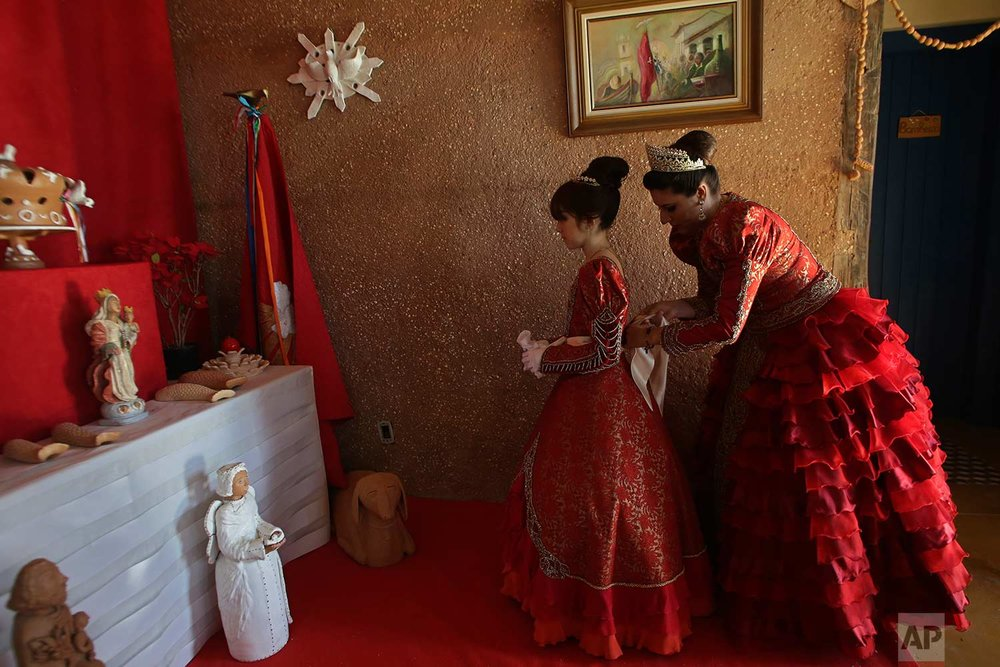 In this Nov. 12, 2017 photo published Friday, Dec. 1, Luana Borges helps her daughter Luana Silva dress for the Azorean Culture Festival, in Enseada de Brito, Brazil. (AP Photo/Eraldo Peres)