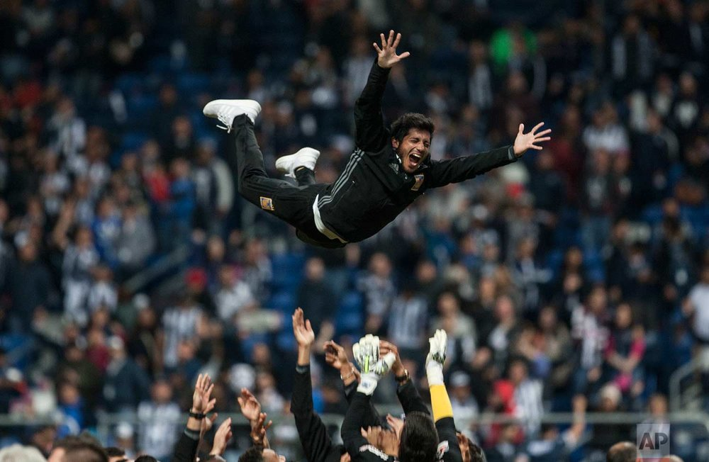 Tigres' soccer player Damian Alvarez is thrown into the air during celebrations after his team's victory over Monterrey and clenching of the Mexican soccer league championship title in Monterrey, Mexico, Sunday, Dec. 10, 2017. (AP Photo/Christian Palma)