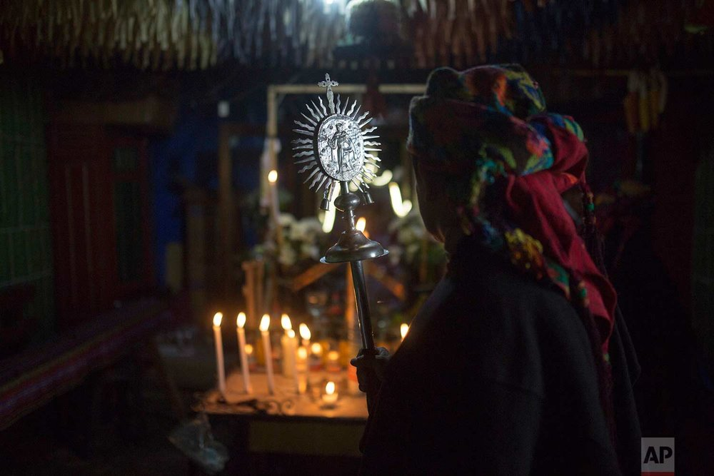 A guardian of St. Thomas holds a scepter decorated with an image of the Saint, as he enters the home of the family that has been caring for the image over the past year, during festivities in honor of the patron Saint of Chichicastenango, Guatemala, Monday, Dec. 18, 2017. (AP Photo/Luis Soto)