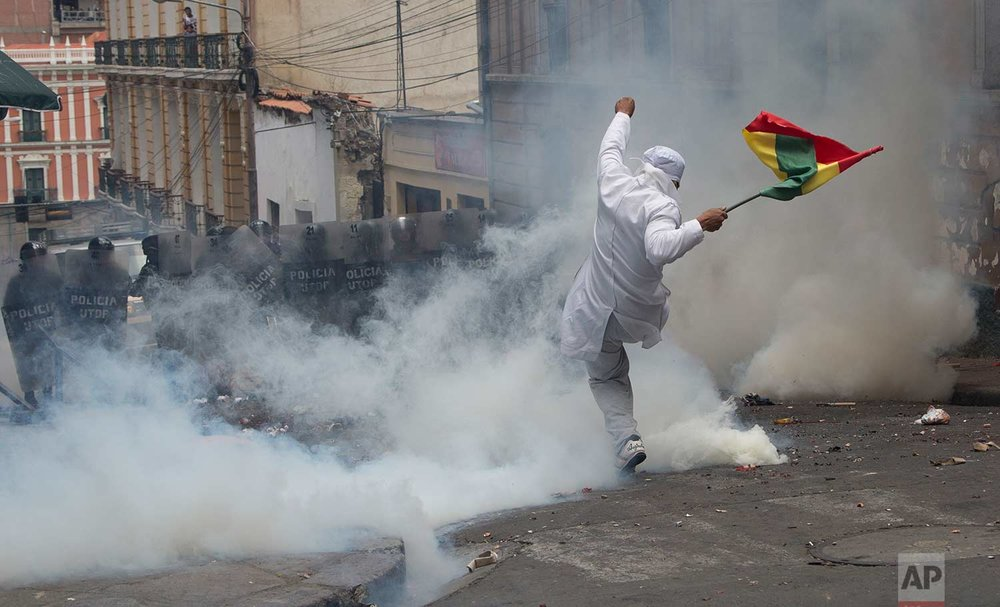 A medical student kicks away a canister of tear gas during clashes with students protesting in solidarity with striking doctors in La Paz, Bolivia. (AP Photo/Juan Karita)