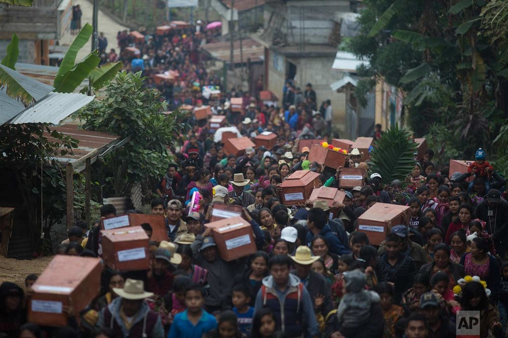 In this Nov. 30, 2017 photos, Ixil Mayans carry the remains of their loved ones killed during the civil war to the cemetery for burial in Santa Avelina, Guatemala. (AP Photo/Luis Soto)