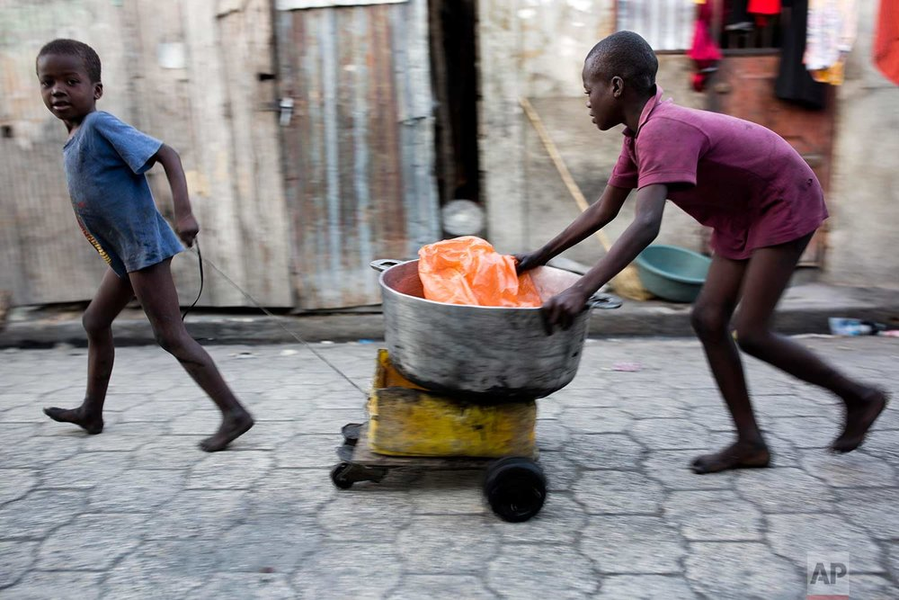 In this Dec. 27, 2017 photo, children transport a cooking bowl for their mother in the Cite Soleil slum of Port-au-Prince, Haiti. Cite Soleil is an extremely impoverished and densely populated slum located in the Port-au-Prince metropolitan area in Haiti. ( AP Photo/Dieu Nalio Chery)