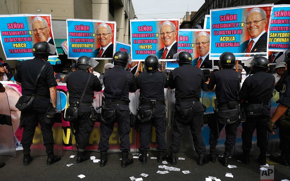 Supporters of Peru's President Pedro Pablo Kuczynski shout slogans as they are held back by the police outside the Peruvian Congress, in Lima, Peru, Thursday, Dec. 21, 2017. (AP Photo/Karel Navarro)