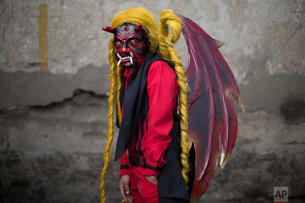Bryan Gonzalez, 14, poses for a portrait in his devil costume at a procession symbolizing the fight between good and evil that celebrates the Virgin of the Immaculate Conception in Ciudad Vieja, Guatemala, Thursday, Dec. 7, 2017. (AP Photo/Luis Soto)