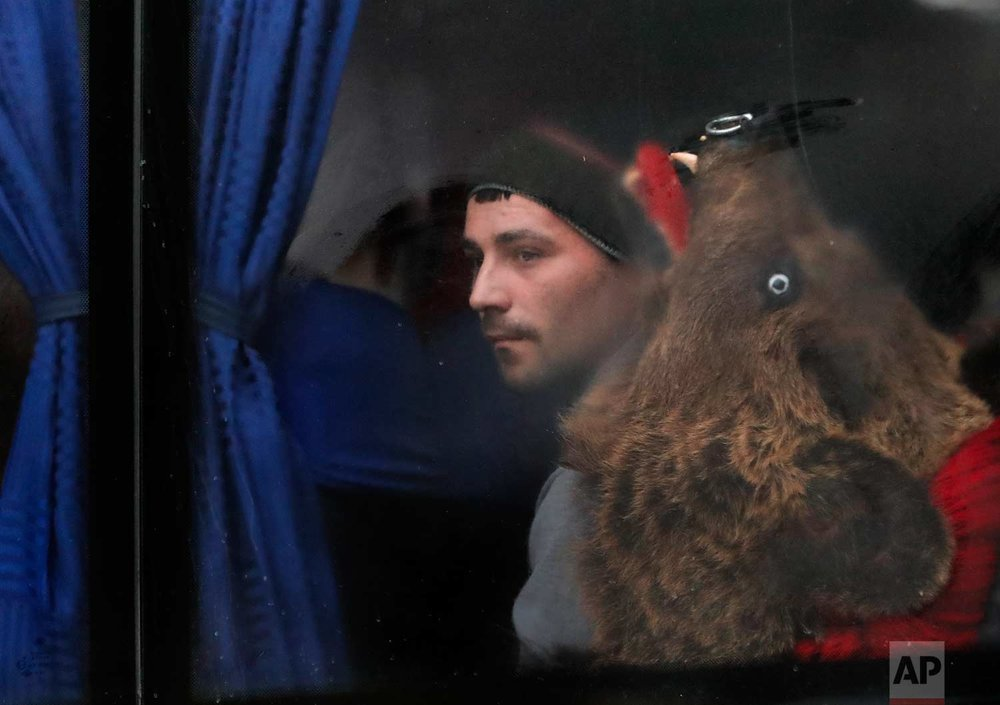 In this Saturday, Dec. 30, 2017, a man wearing a bear fur costume sits on a bus in Comanesti, Romania. (AP Photo/Vadim Ghirda)