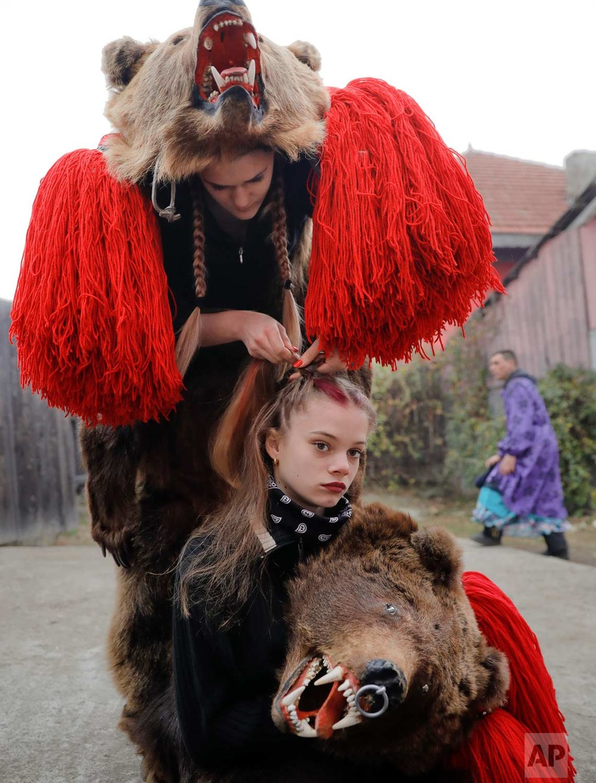 In this Saturday, Dec. 30, 2017, picture, Roxana Stan, top, braids Raluca Atrejei's hair as they get ready for an annual bear parade in Asau, Romania. (AP Photo/Vadim Ghirda)