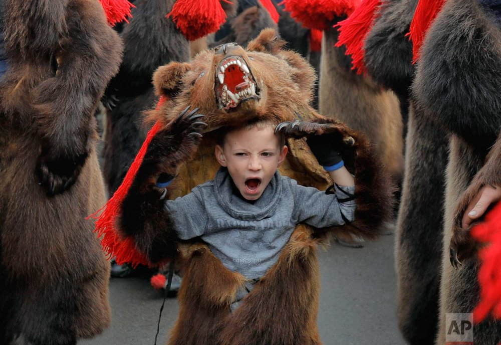 In this Saturday, Dec. 30, 2017, picture a child wearing a bear fur costume yawns while dancing in Comanesti, Romania. (AP Photo/Vadim Ghirda)