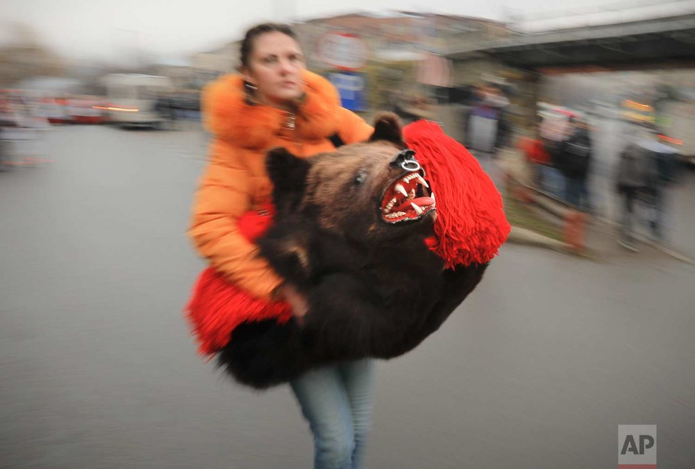 In this Saturday, Dec. 30, 2017, picture, shot with a slow shutter speed, a woman carries a bear fur costume before an annual bear parade in Comanesti, Romania. (AP Photo/Vadim Ghirda)