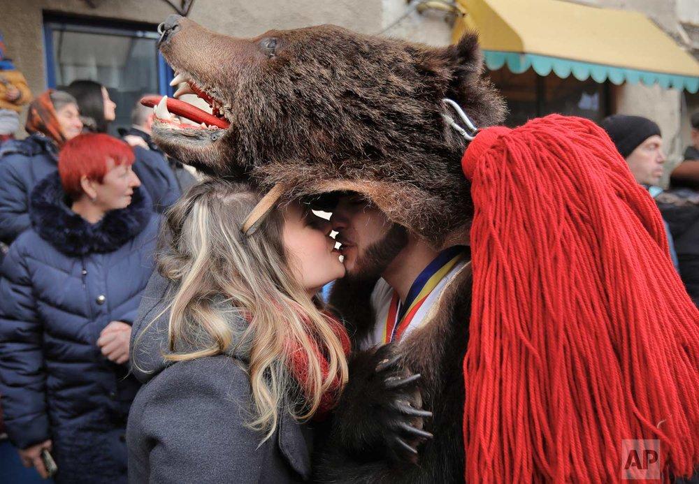 In this Saturday, Dec. 30, 2017, picture a man  wearing a bear fur costume kisses his girlfriend during an annual bear parade in Comanesti, Romania. (AP Photo/Vadim Ghirda)