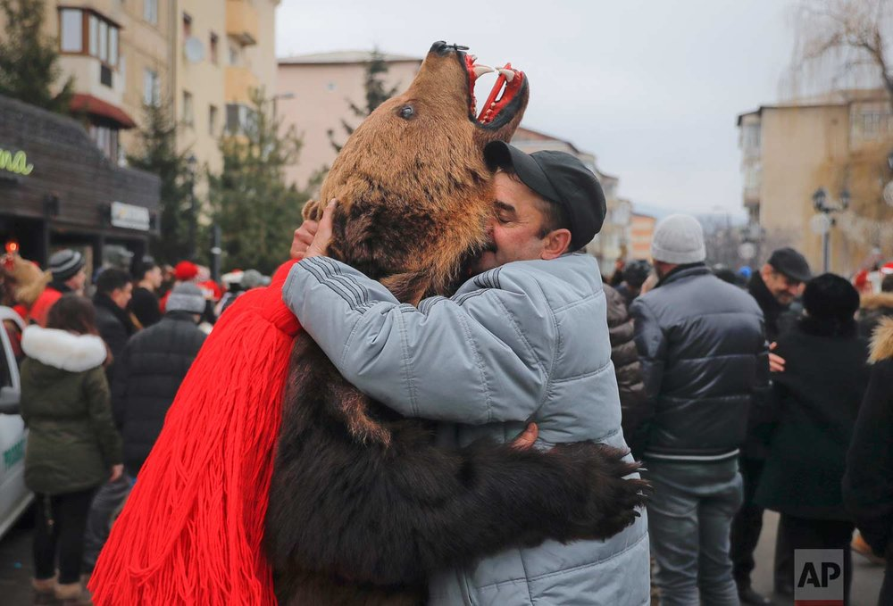 In this Saturday, Dec. 30, 2017, picture men, one wearing a bear fur costume, hug during an annual bear parade in Comanesti, Romania. (AP Photo/Vadim Ghirda)