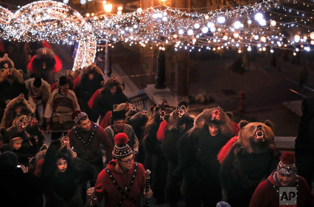 In this Thursday, Dec. 28, 2017, picture people wearing a bear fur costumes walk under Christmas decorations in Piatra Neamt, Romania. (AP Photo/Vadim Ghirda)