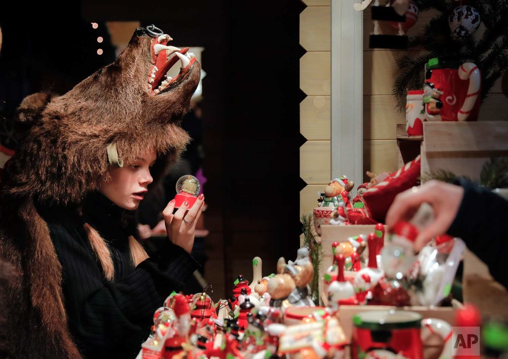 In this Thursday, Dec. 28, 2017, picture Raluca Atrejei, wearing a bear fur costume, looks at an item in a Christmas fair, in Piatra Neamt, Romania. (AP Photo/Vadim Ghirda)