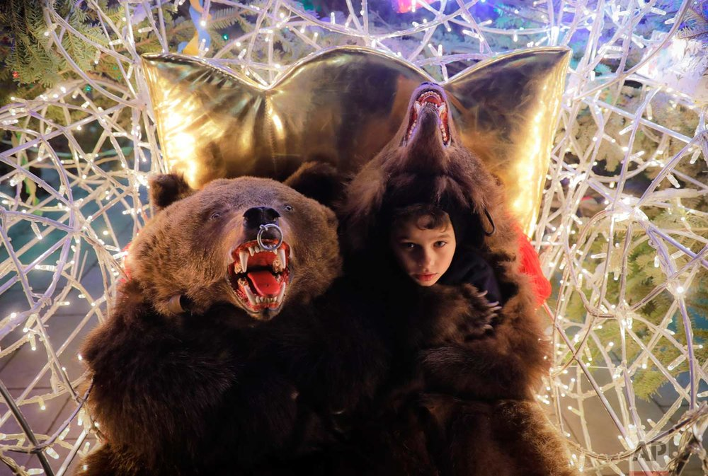 In this Thursday, Dec. 28, 2017, picture children wearing bear fur costumes pose at a Christmas fair, in Piatra Neamt, Romania. (AP Photo/Vadim Ghirda)