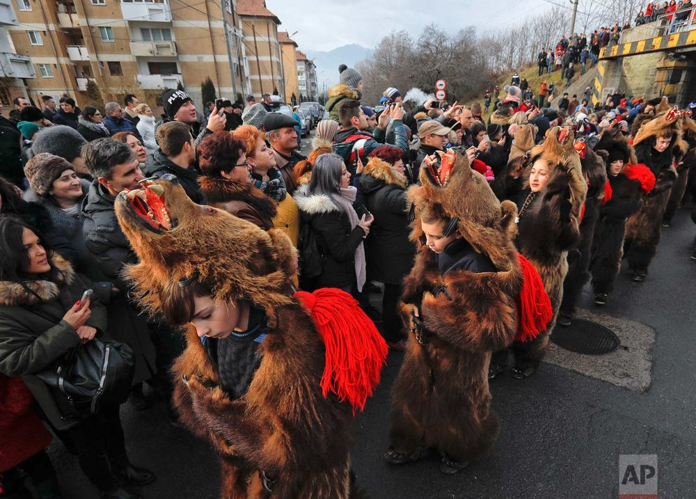 In this Saturday, Dec. 30, 2017, picture people watch an annual bear parade in Comanesti, Romania. (AP Photo/Vadim Ghirda)
