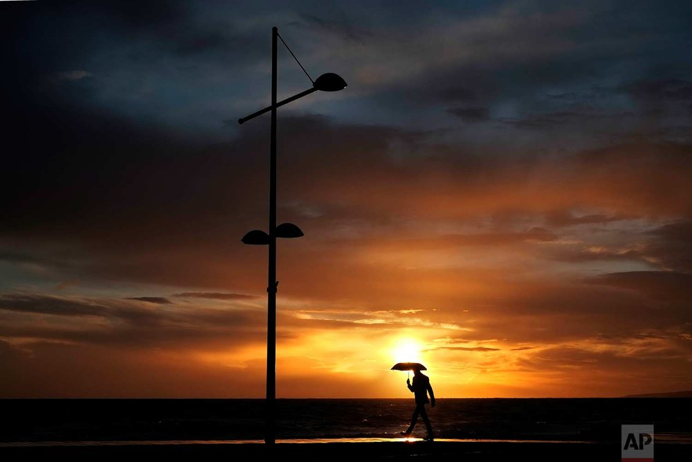 A man with an umbrella walks in the rain as the sun sets at the Ayia Napa resort in the eastern Mediterranean island of Cyprus, Sunday, Dec. 31, 2017. (AP Photo/Petros Karadjias)