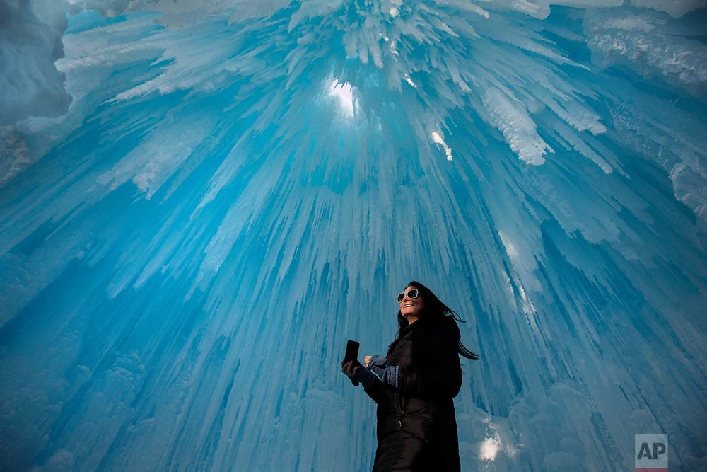 Deanne Ferguson looks at icicles during a tour of the Ice Castles attraction in Edmonton, Alberta, Canada on Thursday, Jan. 4, 2018. (Jason Franson/The Canadian Press via AP)
