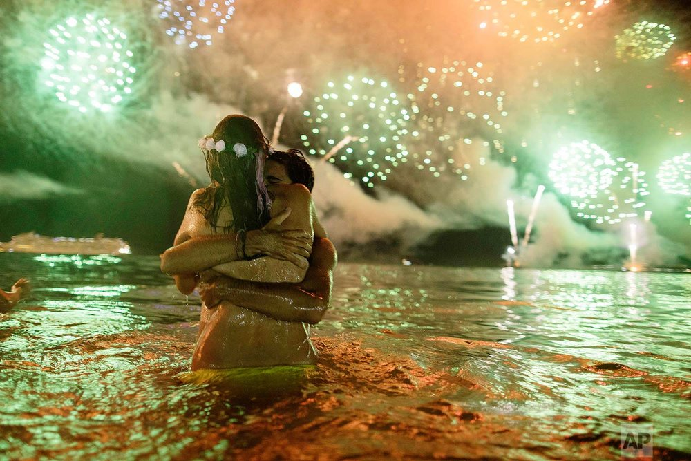 A couple hug each other as they watch fireworks burst over Copacabana beach during New Year's celebrations in Rio de Janeiro, Brazil, on Monday, Jan. 1, 2018. (AP Photo/Leo Correa)