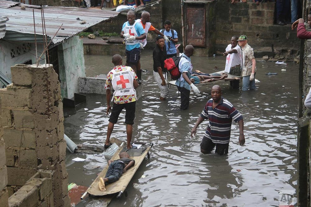 Rescue workers remove bodies of children following floods in Kinshasa, Democratic Republic of Congo, Thursday, Jan. 4, 2018, after a night of heavy rains. Authorities in Congo say dozens have died in and around the capital. (AP Photo/John Bompengo)