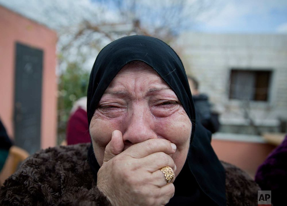 A mourner cries while taking a farewell look at the body of Musab Tamemi, 17, who was killed in clashes with the Israeli army the previous day, during his funeral in the West Bank village of Deir Nizam, near Ramallah, Thursday, Jan. 4, 2018. Israel's military said soldiers opened fire at a protester with a gun during clashes and is reviewing the incident. (AP Photo/Nasser Nasser)