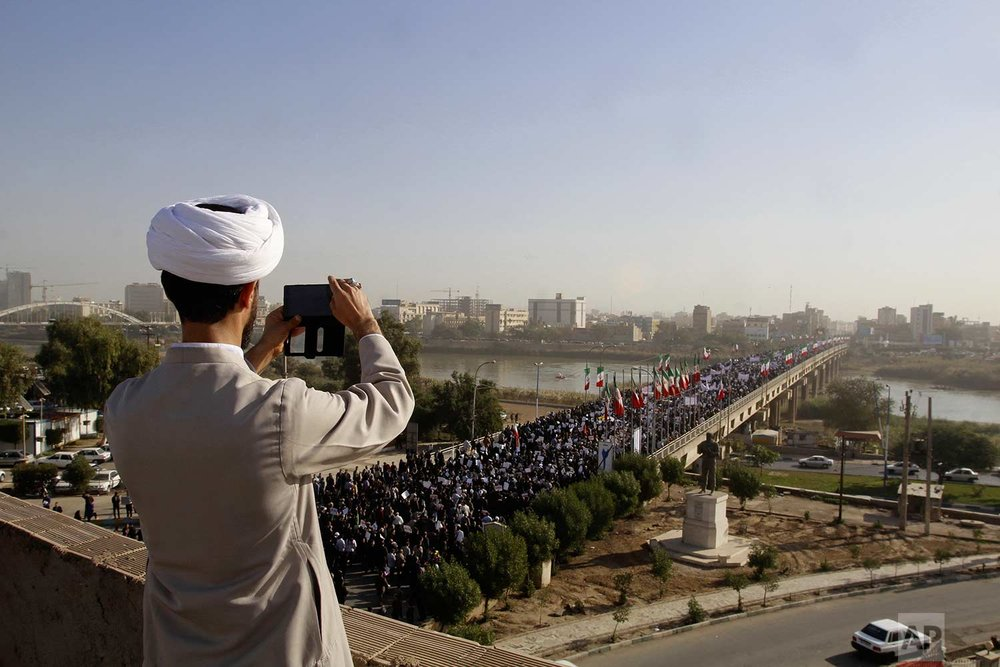 In this photo provided by the Iranian Students' News Agency, a clergyman takes a picture of a pro-government demonstration in the southwestern city of Ahvaz, Iran, Wednesday, Jan. 3, 2018. Tens of thousands of Iranians took part in pro-government demonstrations in several cities across the country on Wednesday, Iranian state media reported, a move apparently seeking to calm nerves after a week of deadly protests and unrest over the country's flagging economy. (Mohammad Ahangari/ISNA via AP)