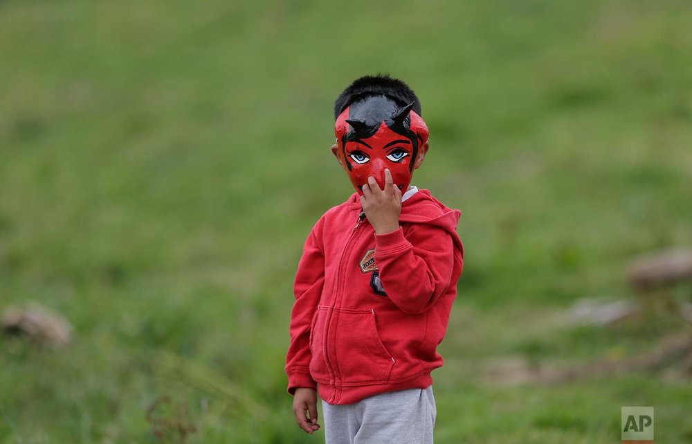 "A boy wearing a devil mask participates in the traditional New Year's festival known as ""La Diablada"", in Pillaro, Ecuador, Friday, Jan. 5, 2018. (AP Photo/Dolores Ochoa)"