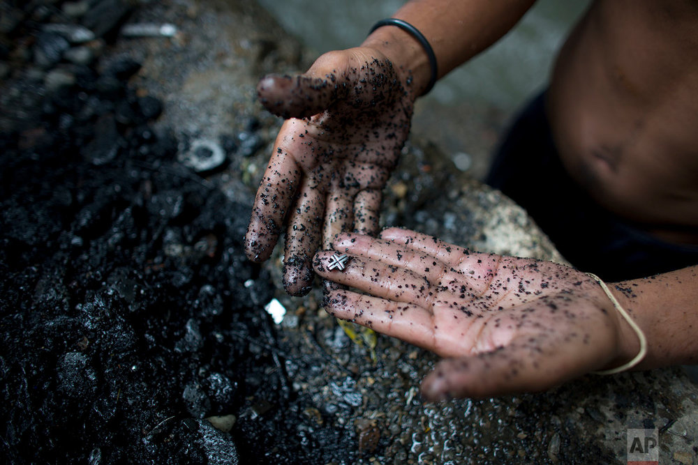 In this Nov. 30, 2017 photo, a river scavenger shows a silver cross he found at the bottom of the polluted Guaire River, in Caracas, Venezuela. Scavengers rake their hands across the river bottom and let the gravel and rocks fall through their fingers, scanning for an earring backing, lost rings or any bits of precious metal to cash in for food. (AP Photo/Ariana Cubillos)