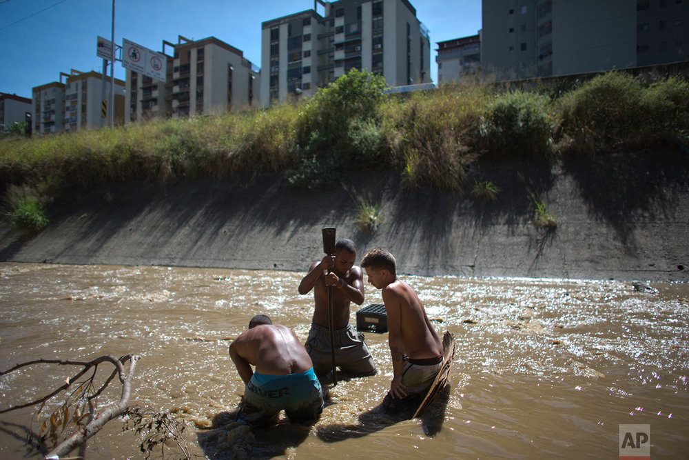 In this Dec. 5, 2017 photo, Angel Villanueva, center, uses a metal bar to break up the mud at the bottom of the polluted Guaire River in Caracas, Venezuela. The 25-year old says people don't want to touch him, or come near because they fear they'll get an infection from him from being in the river, but that he doesn't know of anybody who has died from scavenging the water. (AP Photo/Ariana Cubillos)