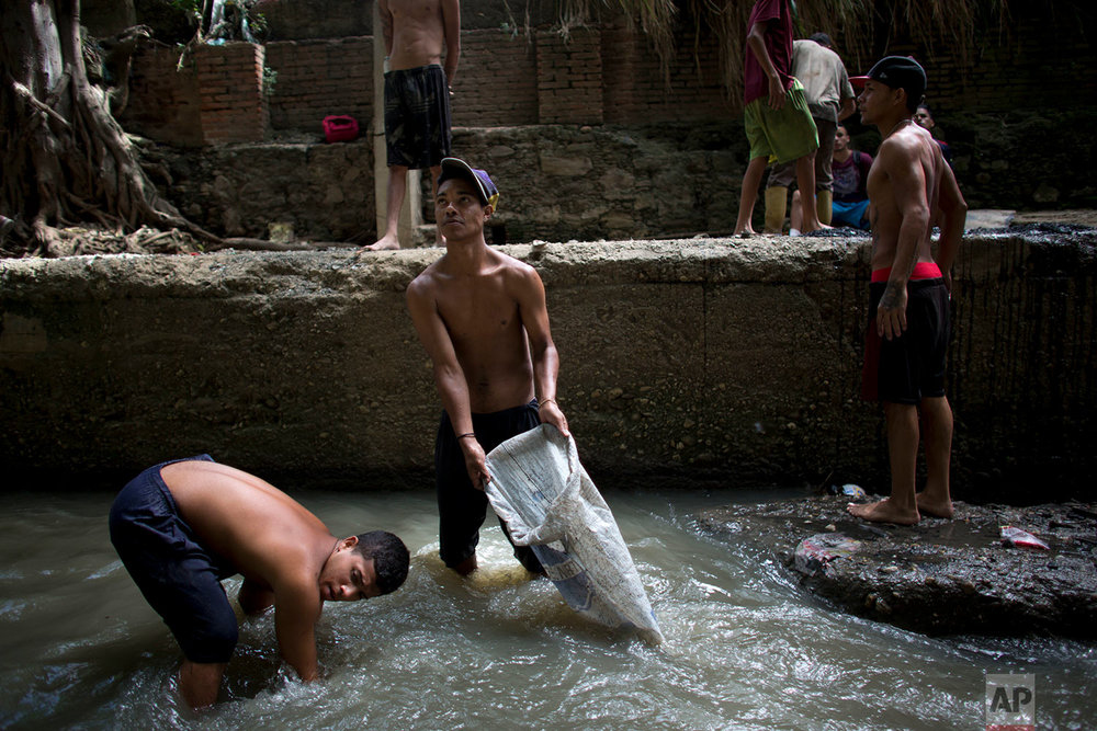 In this Nov. 30, 2017 photo, Douglas, center, holds a sack in the polluted Guaire River as he and others pull mud up from the bed of the river in search of gold and other valuables to sell, in Caracas, Venezuela. The river and the scavengers in it go largely unseen by Caracas residents speeding overhead on the city's main highway, blocked from view by concrete barriers. (AP Photo/Ariana Cubillos)