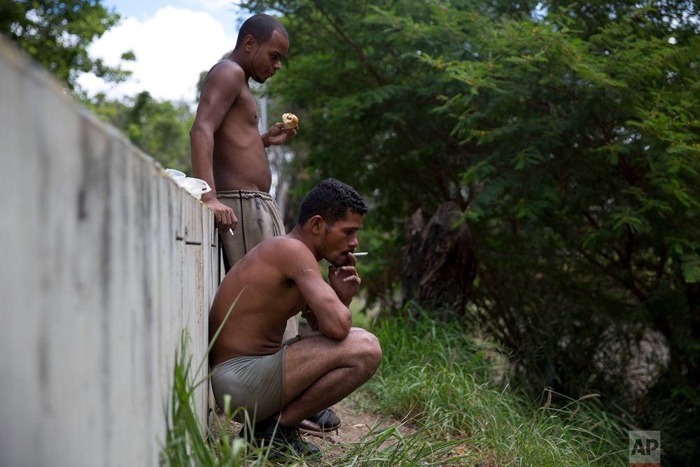 "In this Dec. 7, 2017 photo, Felix Diaz smokes a cigarette next to Angel Villanueva eating a piece of bread as they take a break from scraping the bottom of the polluted Guaire River in search of gold and anything of value to sell, in Caracas, Venezuela. ""Working in the Guaire isn't easy. It's hard,"" said 25-year-old Villanueva. ""When it provides, it provides. When it takes, it takes your life,"" referring to flash flooding. Diaz, a former security guard who lives with his sister, said he started searching the river nine months ago. (AP Photo/Ariana Cubillos)"
