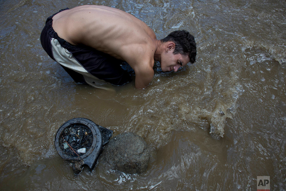In this Dec. 5, 2017 photo, David Garcia keeps his head just barely above water as he scrapes the bottom of the polluted Guaire River in search of gold and anything of value to sell in Caracas, Venezuela. The 19-year-old father of a 4-month-old baby said it was his first week working in the toxic, sewage filled waters and that his family didn't know this was how he was trying to earn money to put food on the table. (AP Photo/Ariana Cubillos)