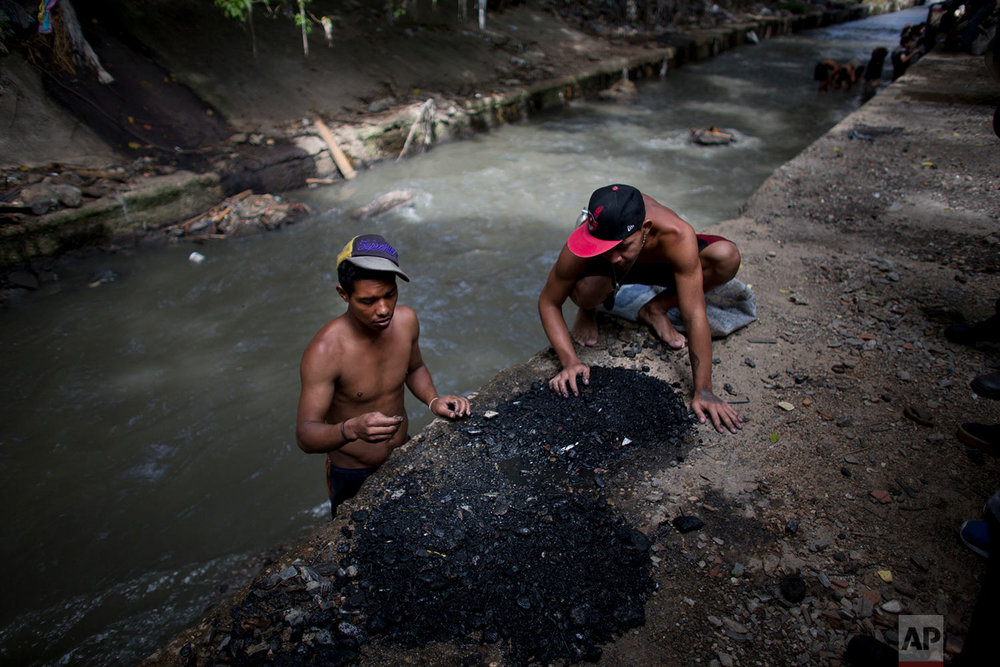 In this Nov. 30, 2017 photo, men sort through the debris they pulled up from the bottom of the polluted Guaire River, in search of pieces of gold and anything of value to sell in Caracas, Venezuela. Venezuela sits atop the world's largest oil reserves, but the global drop in crude prices and plummeting production under nearly two decades of socialist rule has left many in the country of 30 million people struggling to survive. (AP Photo/Ariana Cubillos)