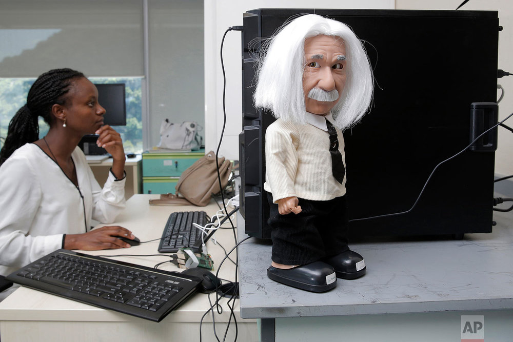 In this Sept. 28, 2017 photo, one of the Hanson Robotics' creations, Professor Einstein, an educational robot launched last year aimed at kids, is seen next to a staff member in Hong Kong.  (AP Photo/Kin Cheung)  |  See these photos on AP Images