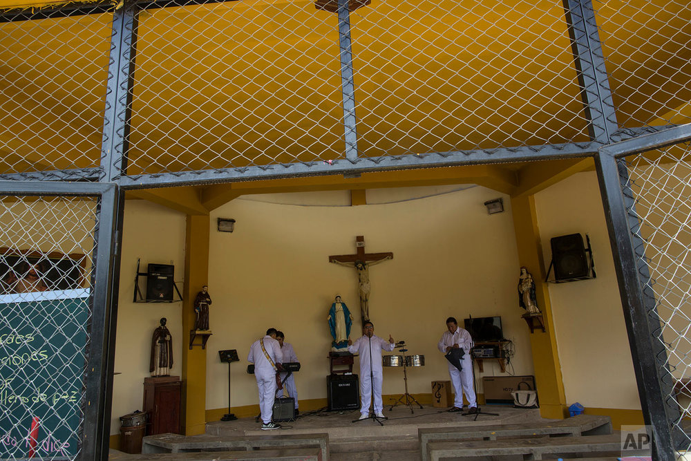 """In this Jan. 12, 2018 photo, inmate and member of the band """"Sin Limites,"""" or Without Limits, rehearses the song """"Esperanza y Amor,"""" or Hope and Love, created by the prison musical group especially for the visit by Pope Francis, at the jai's chapel in Puerto Maldonado, Madre de Dios province, Peru. Prisoners convicted of crimes like robbery and drug trafficking at this prison in the Peruvian Amazon are also using their time behind bars to build simple wooden chairs that indigenous leaders will use while meeting with Pope Francis. (AP Photo/Rodrigo Abd)