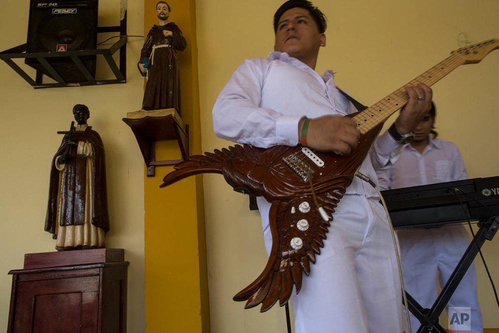 """In this Jan. 12, 2018 photo, inmate and member of the band """"Sin Limites,"""" or Without Limits, rehearses the song """"Esperanza y Amor,"""" or Hope and Love, created by the prison musical group especially for the visit by Pope Francis in Puerto Maldonado, Madre de Dios province, Peru. His guitar was built in the jail's wood shop. (AP Photo/Rodrigo Abd)