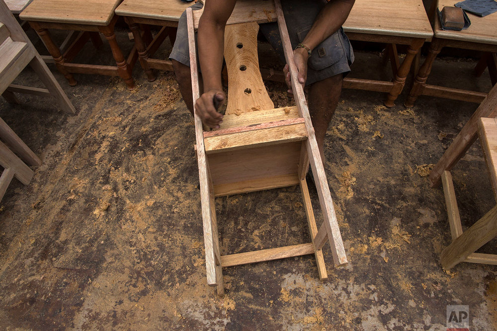In this Jan. 12, 2018 photo, an inmate builds a chair to be used by guests who will attend events with Pope Francis in Puerto Maldonado, Madre de Dios province, Peru. More than a hundred inmates were commissioned by the Catholic Church to build 350 chairs that will be placed inside a coliseum in Puerto Maldonado, a gateway into the Amazon rainforest that Francis is scheduled to visit on Friday. (AP Photo/Rodrigo Abd)| See these photos on AP Images