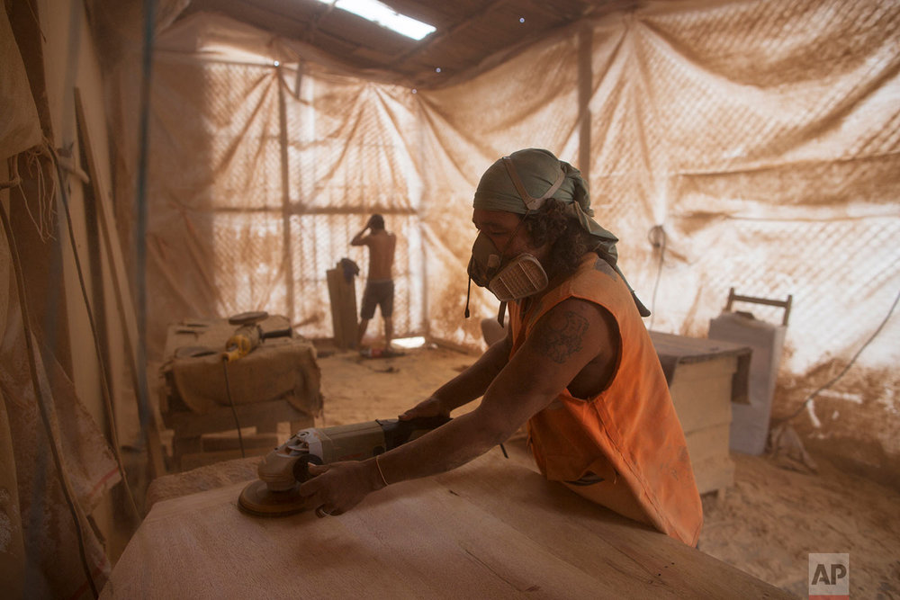 In this Jan. 12, 2018 photo, inmate Roy Ruiz Flores, 44, sands wood as he helps build the chairs to be used by indigenous leaders during Pope Francis's visit in Puerto Maldonado, Madre de Dios province, Peru. The chairs are made of wood from Amazon forests where illegal gold mining and deforestation threaten the delicate ecosystem. (AP Photo/Rodrigo Abd) |  See these photos on AP Images