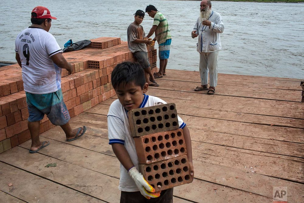 """In this Jan. 8, 2018 photo, Father Pablo Zabala, better known as Padre Pablo, chats with workers offloading bricks brought across a boat on the Inambari River, in Puerto Carlos, part of Peru's Madre de Dios region in the Amazon. The 70-year-old Spanish priest says he had long felt compelled to work not just with the righteous, but the sinners, and to connect with """"the life of the common people."""" (AP Photo/Rodrigo Abd) 