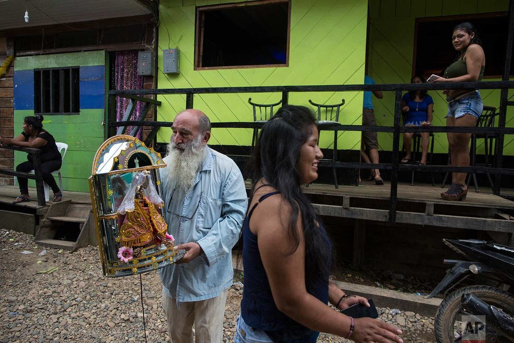 In this Jan. 10, 2018 photo, Father Pablo Zabala, better known as Padre Pablo, walks to the Barrio Chino bar to return a statue of Our Lady of Forgetfulness, Triumph and Mercy, adopted by the local sex workers as their patron saint, in Boca Colorado, part of Peru's Madre de Dios region in the Amazon. (AP Photo/Rodrigo Abd) |  See these photos on AP Images