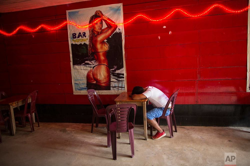 In this Jan. 10, 2018 photo, a client sits passed out at the Nectar del Olvido bar, in Boca Colorado, part of Peru's Madre de Dios region in the Amazon. (AP Photo/Rodrigo Abd) |  See these photos on AP Images