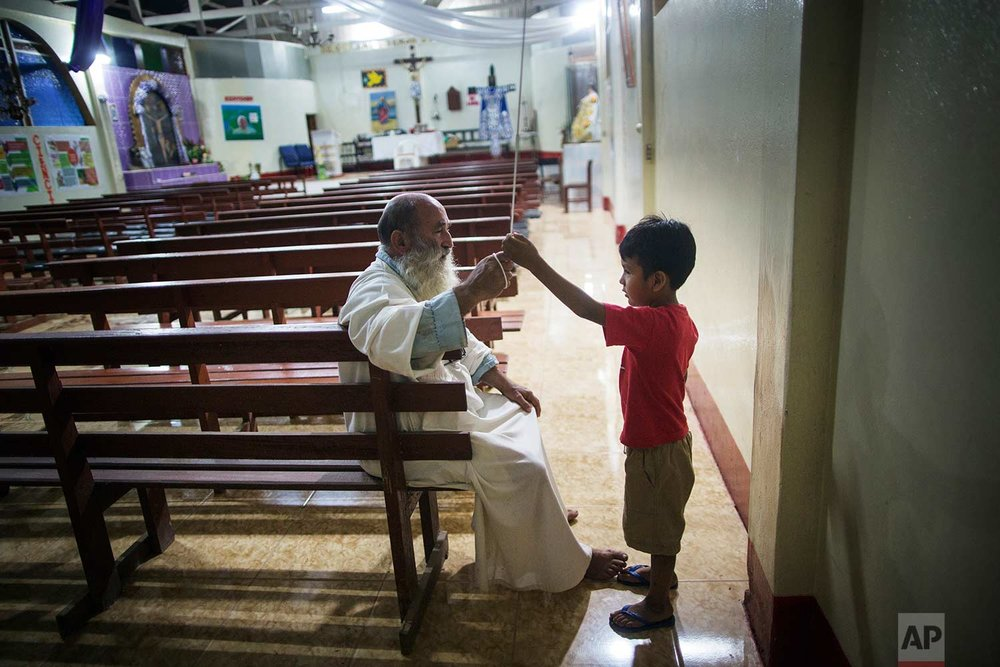 In this Jan. 13, 2018 photo, Father Pablo Zabala, better known as Padre Pablo, explains to five-year-old Valentino Cahuata how to properly ring the church bell to call the faithful to Mass, in Boca Colorado, part of Peru's Madre de Dios region in the Amazon.(AP Photo/Rodrigo Abd) | See these photos on AP Images