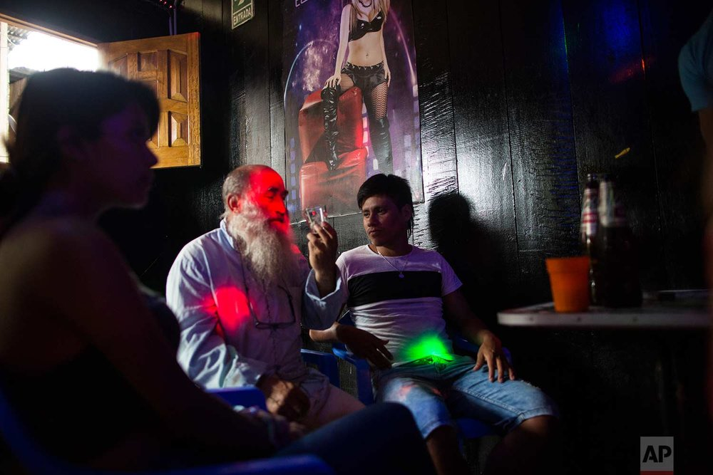 In this Jan. 10, 2018 photo, Father Pablo Zabala, better known as Padre Pablo, drinks a beer at the Nectar del Olvido bar, invited by men accompanied by sex workers in Boca Colorado, part of Peru's Madre de Dios region in the Amazon.(AP Photo/Rodrigo Abd) | See these photos on AP Images