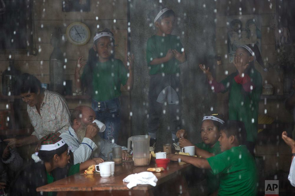 In this Jan. 6, 2018 photo, Father Pablo Zabala, better known as Padre Pablo, drinks a cup of hot chocolate as children practice a musical presentation at the parish in Boca Colorado, part of Peru's Madre de Dios region in the Amazon. Pope Francis is expected to visit the region Friday, Jan. 19, and deliver a speech encouraging Peruvians to protect the world's largest rainforest. The 70-year-old Spanish priest says his congregation of miners is unlikely to welcome Francis' message. (AP Photo/Rodrigo Abd) |  See these photos on AP Images