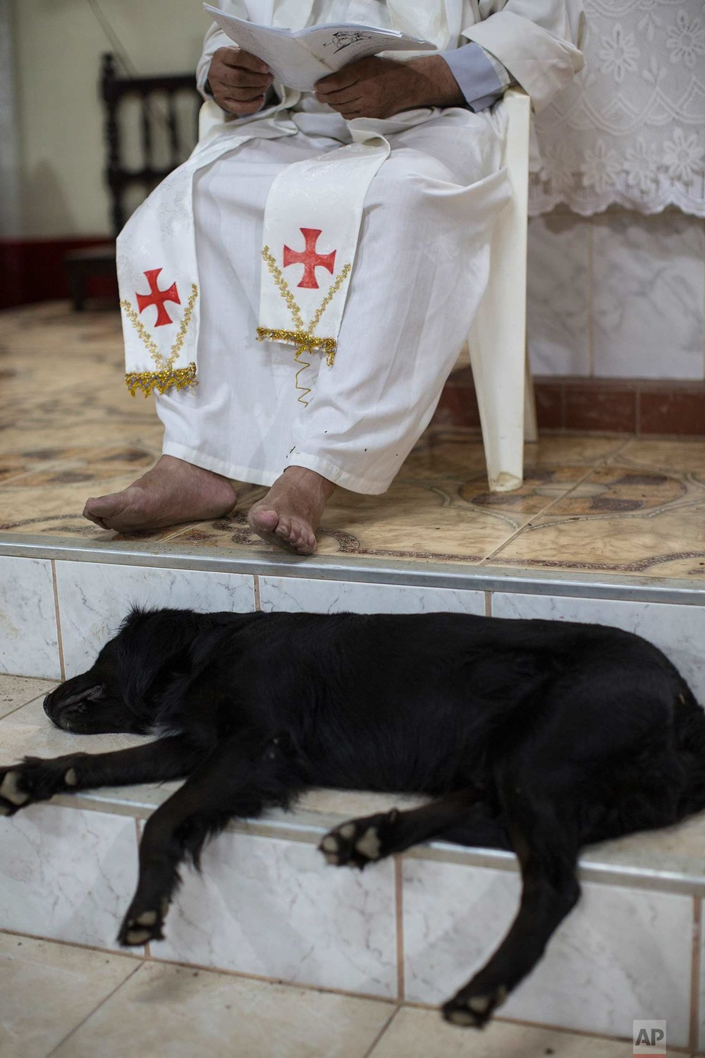 In this Jan. 6, 2018 photo, Father Pablo Zabala, better known as Padre Pablo, celebrates a Mass as his dog naps on the steps of the altar in Boca Colorado, part of Peru's Madre de Dios region in the Amazon. Known for his eccentric style, the 70-year-old Spanish priest often celebrates Mass barefooted and with his pet dog Neron at his side. (AP Photo/Rodrigo Abd) |  See these photos on AP Images