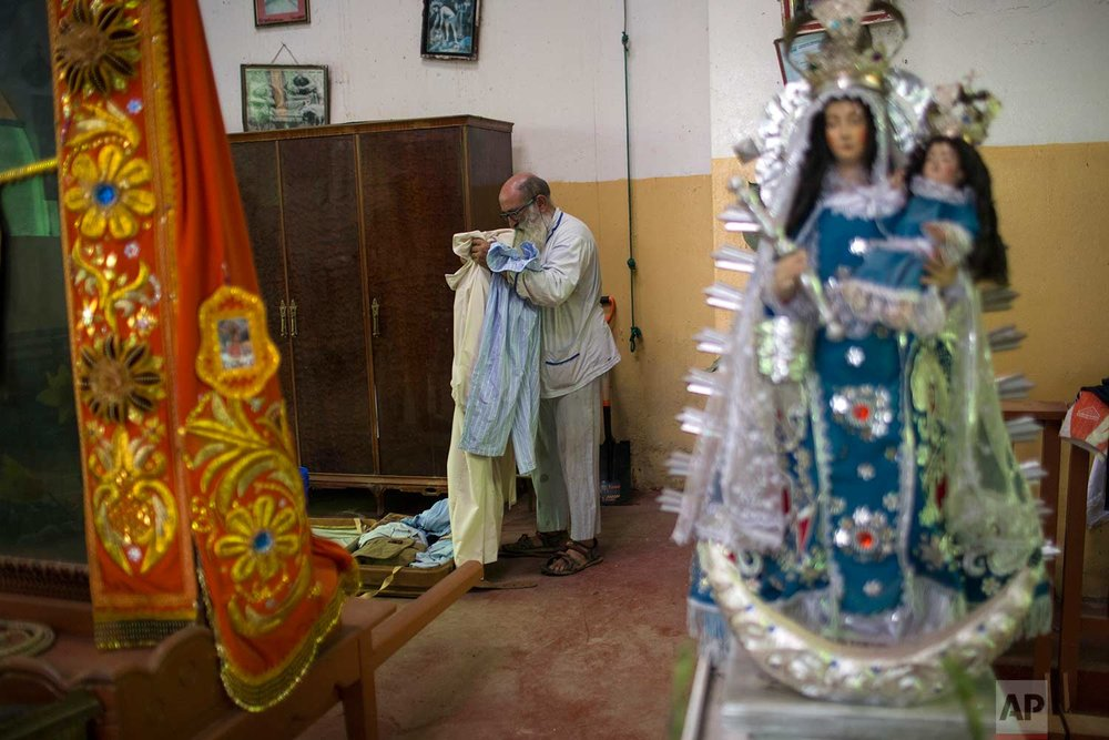 In this Jan. 14, 2018 photo, Pablo Zabala, better known as Padre Pablo, packs his more than 30 pairs of pajamas into a suitcase in the sacristy of the Senor de Qoyllority Catholic Church, in Puerto Carlos, part of Peru's Madre de Dios province in the Amazon. The 70-year-old Spanish priest credits women who labor as sex workers in nearby bars with helping build two churches and has encouraged them to pray to Mary Magdalene. Each year he takes a sculpture of the woman considered Jesus' most important female disciple into a local bar as part of a religious procession. (AP Photo/Rodrigo Abd) |  See these photos on AP Images