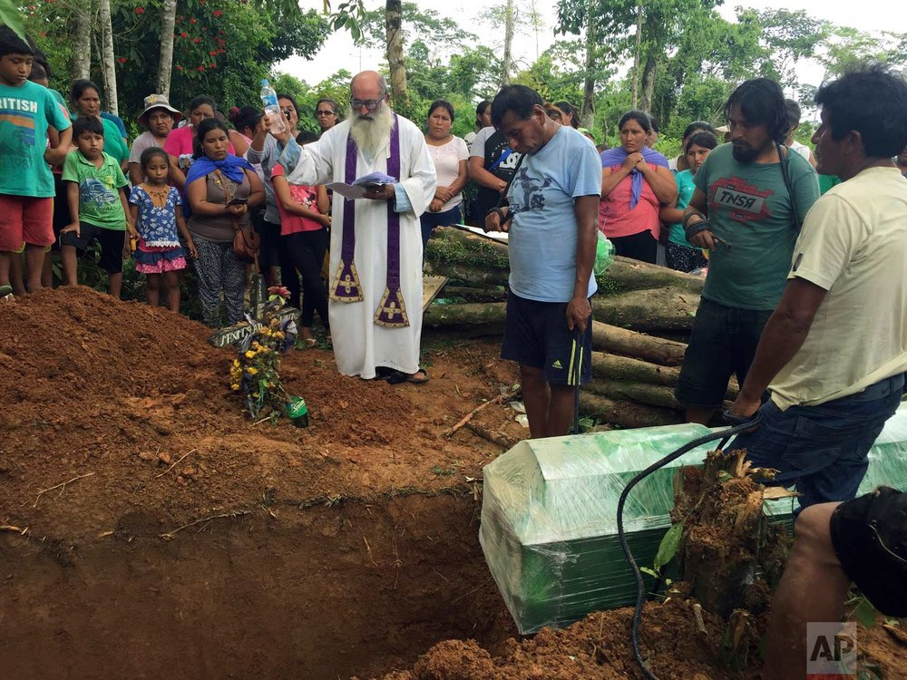 In this Jan. 6, 2018 photo, Father Pablo Zabala, better known as Padre Pablo, presides over a burial service for miner Juan Peralta at the Delta 1 cemetery, in Peru's Madre de Dios region. The 70-year-old Spanish priest tends to some of the rainforest's most hapless souls, like Juan Peralta, who was shot dead in a dispute with an indigenous tribe and had no wife or children to mourn him. (AP Photo/Franklin Briceno) | See these photos on AP Images