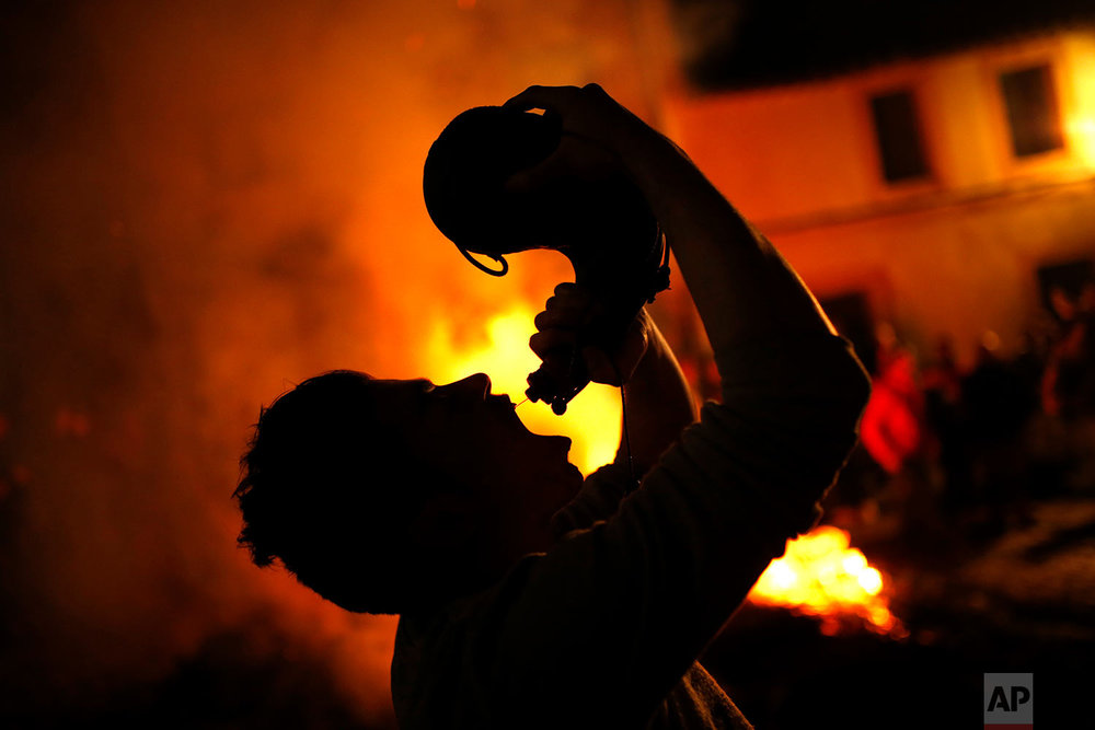 A man drinks wine from a wineskin next to bonfires during the ritual in honor of Saint Anthony the Abbot in San Bartolome de Pinares, Spain, Tuesday, Jan. 16, 2018. (AP Photo/Francisco Seco)| See these photos on AP Images