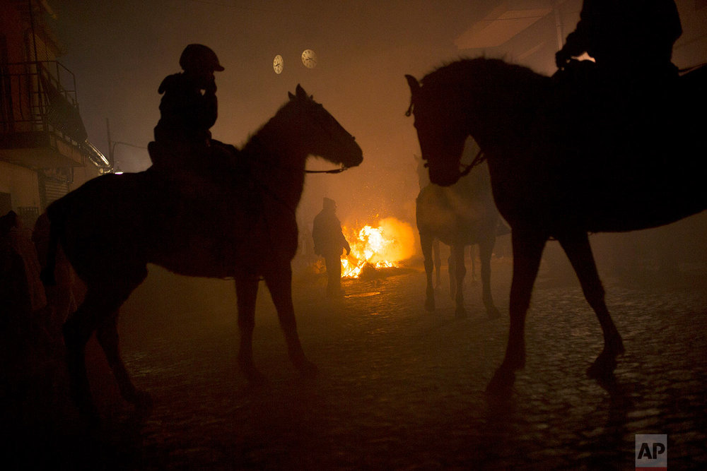 Riders and horses stand by bonfires prior the ritual in honor of Saint Anthony the Abbot, the patron saint of animals, in San Bartolome de Pinares, Spain, Tuesday, Jan. 16, 2018. (AP Photo/Francisco Seco) |  See these photos on AP Images