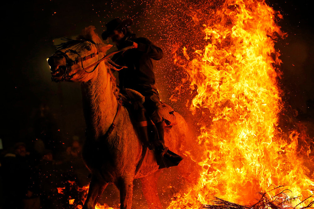 A man rides a horse through a bonfire as part of a ritual in honor of Saint Anthony the Abbot, the patron saint of animals, in San Bartolome de Pinares, Spain, Tuesday, Jan. 16, 2018. (AP Photo/Francisco Seco)| See these photos on AP Images
