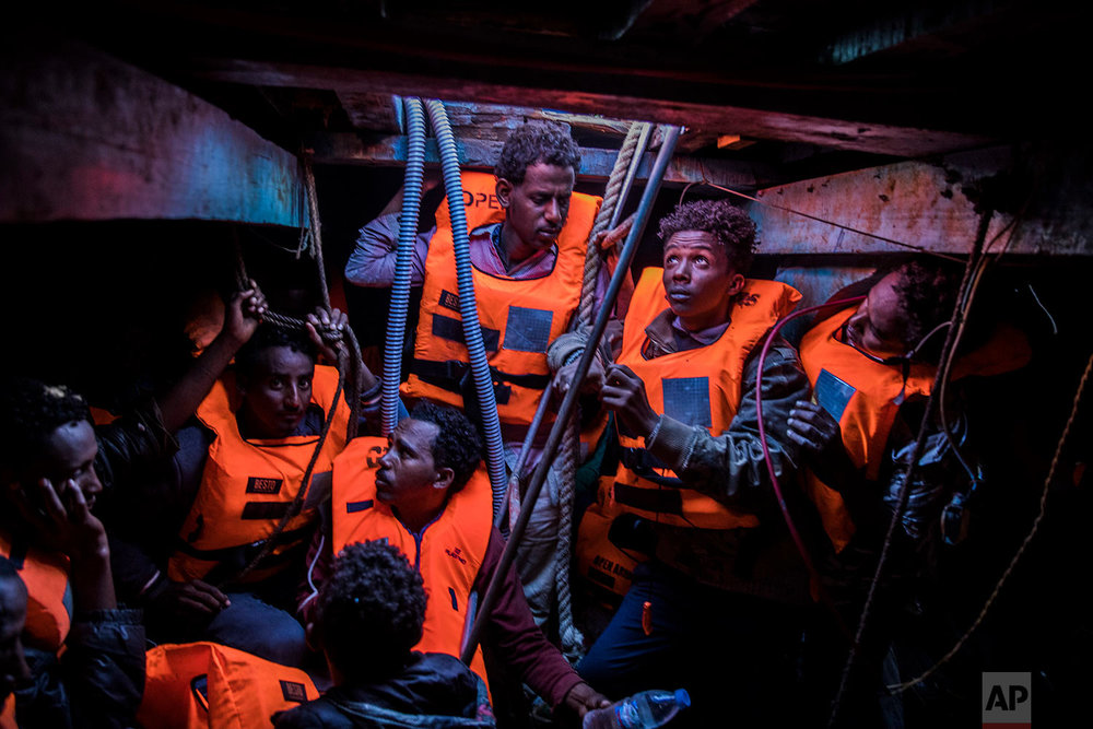 In this Tuesday, Jan. 16, 2018 photo Sub-Saharan refugees and migrants, mostly from Eritrea, wait to be rescued by aid workers of Spanish NGO Proactiva Open Arms, in the lower deck of a wooden as they were trying to leave the Libyan coast and reach European soil, 34 miles north of Kasr-El-Karabulli, Libya. (AP Photo/Santi Palacios)