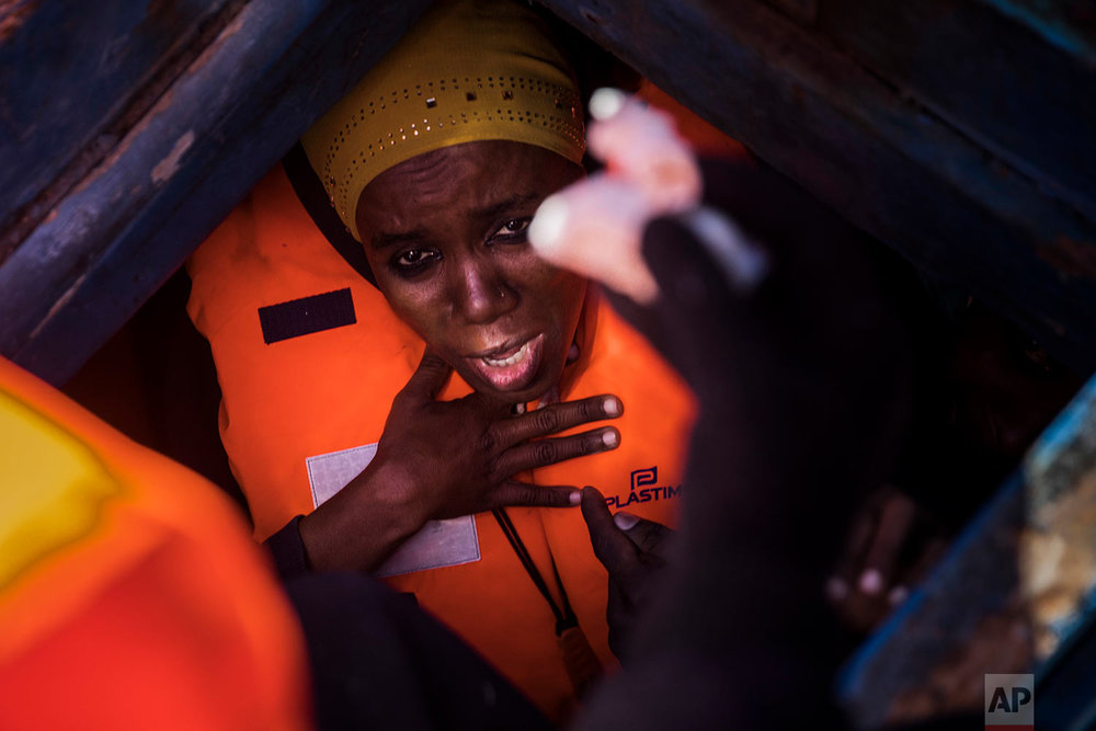 In this Tuesday, Jan. 16, 2018 photo a woman from Eritrea tries to breathe inside the lower deck of a wooden boat with 450 people aboard, as they were trying to leave the Libyan coast and reach European soil, 34 miles north of Kasr-El-Karabulli, Libya. (AP Photo/Santi Palacios)